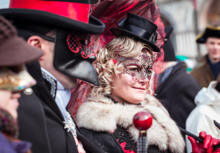 a woman in an red and black mask with an intricate lace design at venice carnival