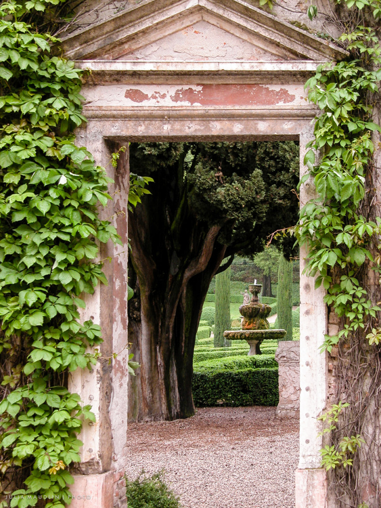 A fountain seen through an ancient arch in the Giardino Giusti in Verona