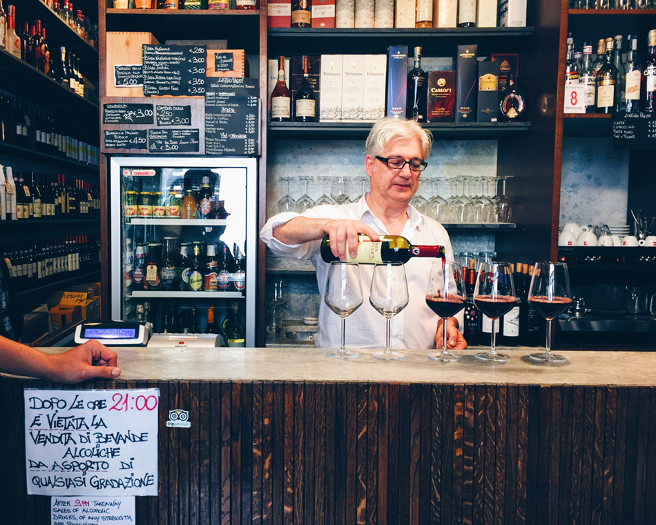 A white haired man standing behind a shop counter pours red wine in five glasses