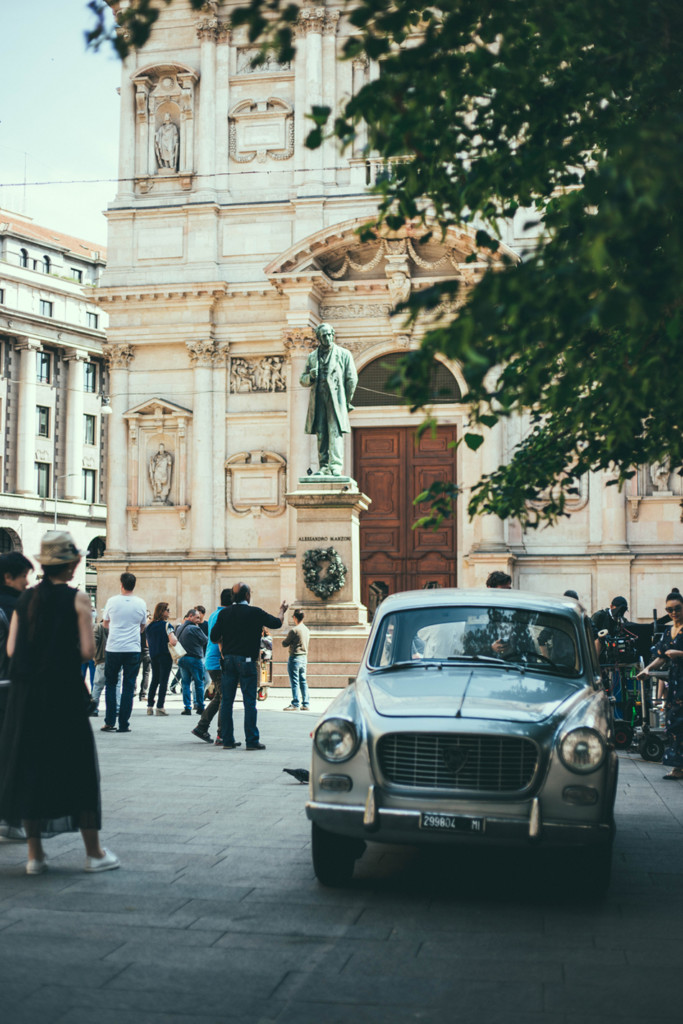 People walk past a vintage car parked in an Italian piazza while doing lo struscio