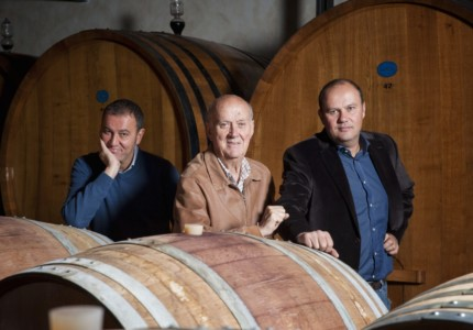 Alberto, Michele and Stefano Chiarlo standing amongst barrels of ageing wine