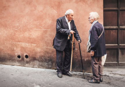 An old man and an old woman standing facing each other on a street