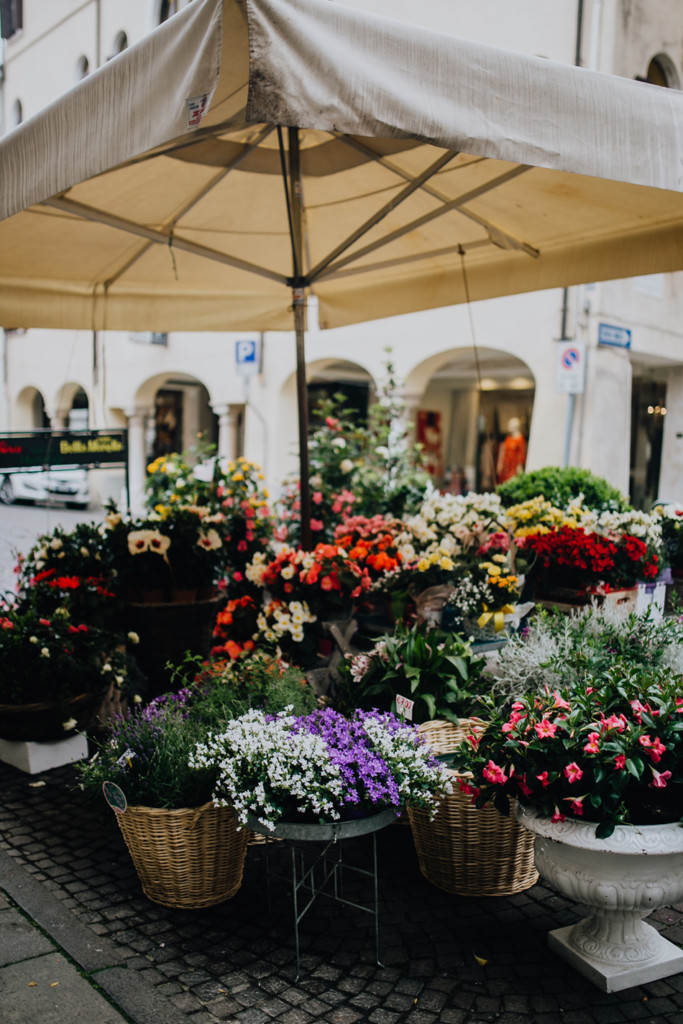 A street corner stand with various multi-coloured bouquets of flowers under a patio umbrella