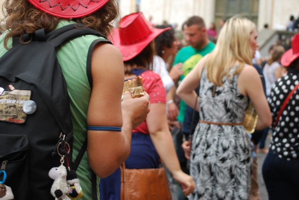 A woman in a crowd of people holding a sandwich at an Italian food festival