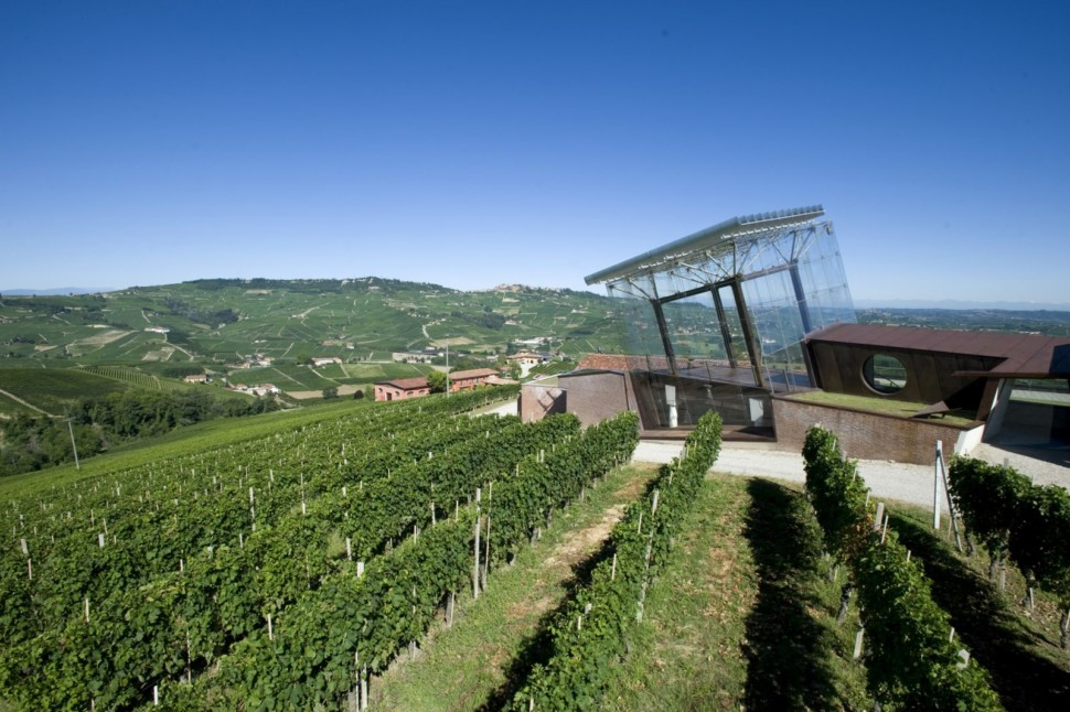 A glass cube structure overlooking vineyards in Italy
